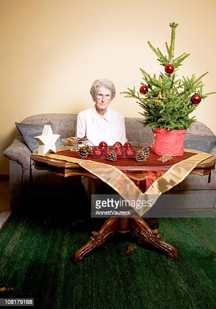 Senior Woman Sitting Alone with Christmas Tree and Decorations