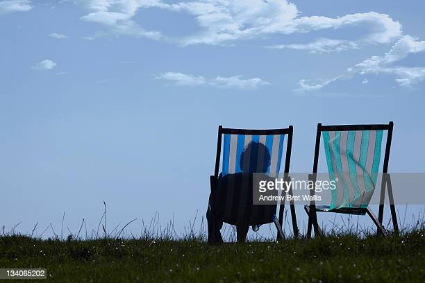senior woman sitting alongside an empty deckchair - one senior woman only stock pictures, royalty-free photos & images