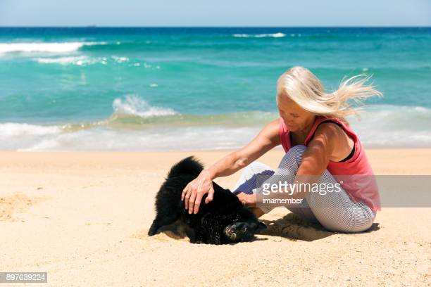Senior woman sitting and playing with dog on the beach