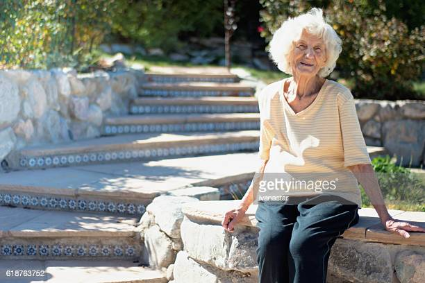 Senior woman sitting and smiling in the yard