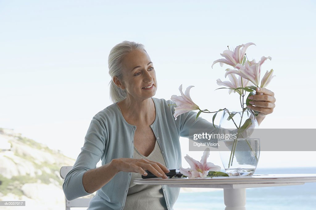 Senior Woman Sitting at a Table and Pruning Cut Flowers : Stock Photo