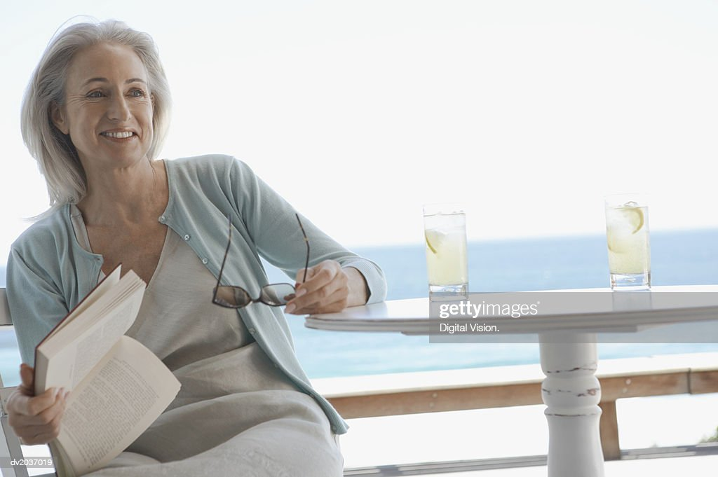 Senior Woman Sitting at a Table Holding a Book and Sunglasses with the Sea in the Background : Stock Photo