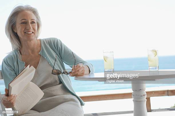Senior Woman Sitting at a Table Holding a Book and Sunglasses with the Sea in the Background