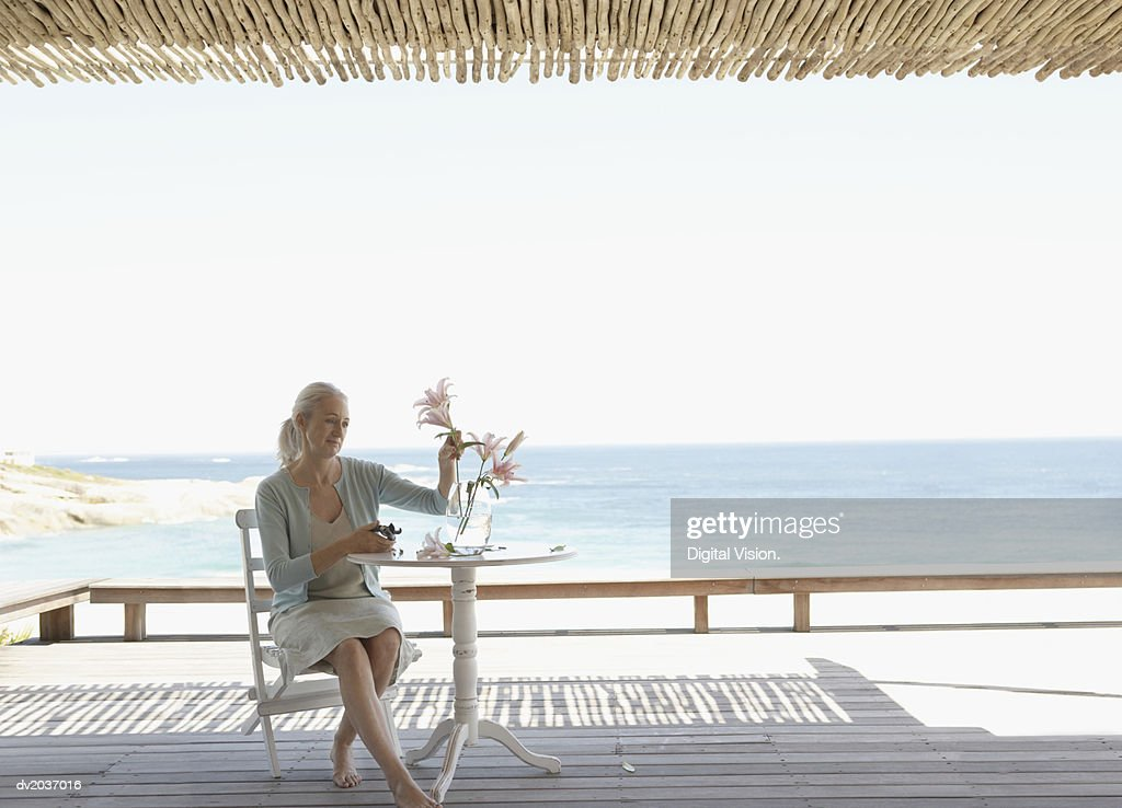 Senior Woman Sitting at a Table on a Patio and Pruning Cut Flowers : Stock Photo