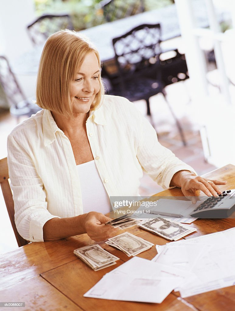 Senior Woman Sitting at a Wooden Kitchen Table, Using a Calculator to Organise Her Personal Finances : Stock Photo