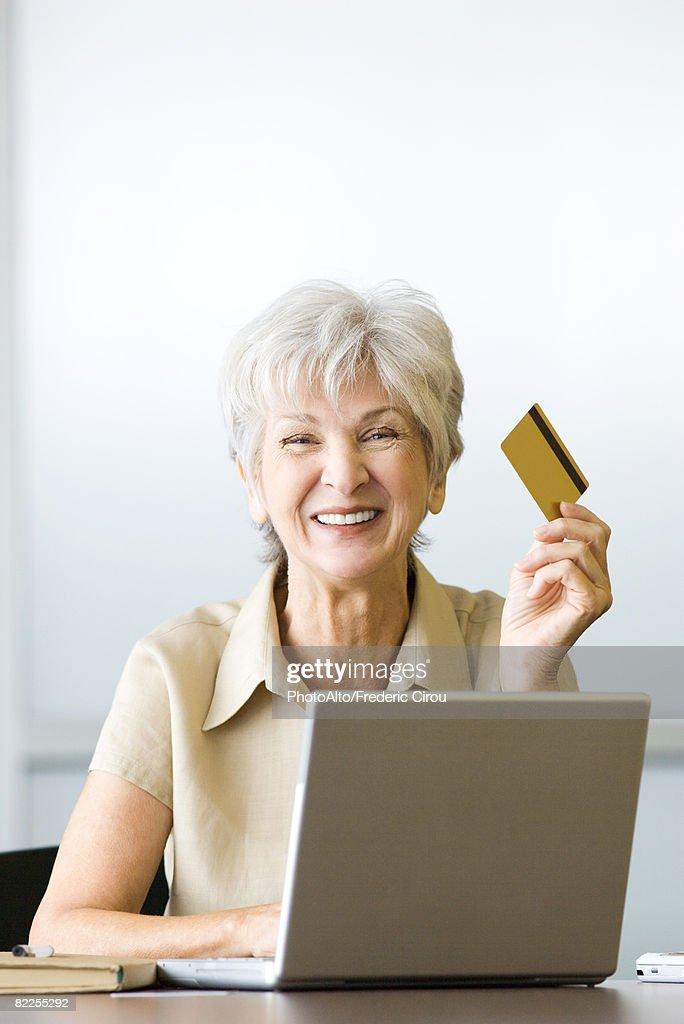 Senior woman sitting at desk, holding credit card, using laptop, smiling at camera : Stock Photo