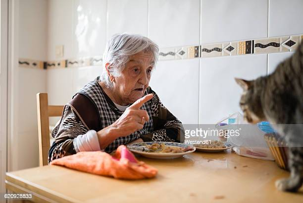 Senior woman sitting at dining table scolding her cat