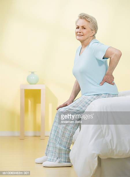 Senior woman sitting at edge of bed with hand on back, portrait