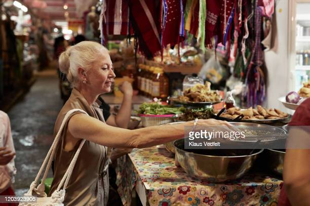 senior woman sitting at fast food stall in market - curiosity stock pictures, royalty-free photos & images