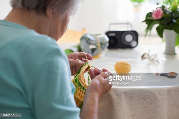 Senior woman sitting at kitchen table, crocheting potholders