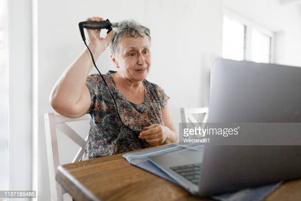 senior woman sitting at table at home using laptop and doing her hair - tutorial stock pictures, royalty-free photos & images
