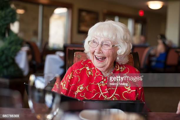 senior woman sitting at table in restaurant, laughing - texas independence day stock pictures, royalty-free photos & images