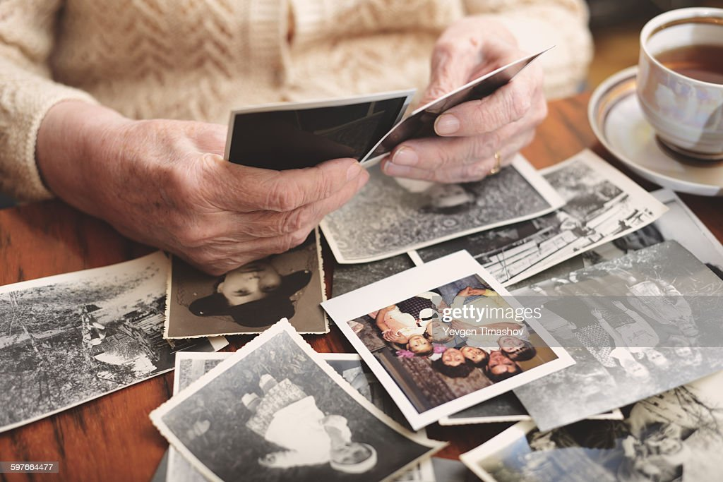 Senior woman sitting at table, looking through old photographs, mid section : Stock Photo