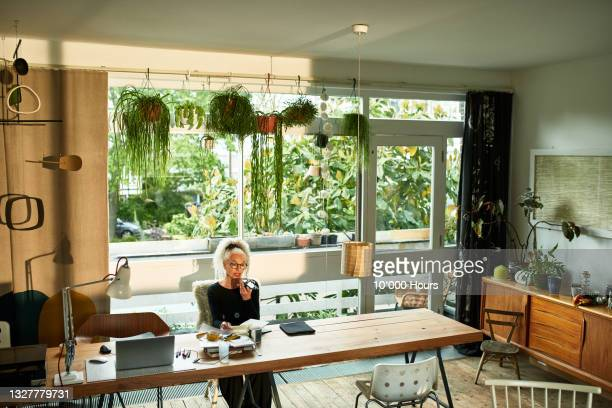 senior woman sitting at table using mobile phone - working seniors stock pictures, royalty-free photos & images