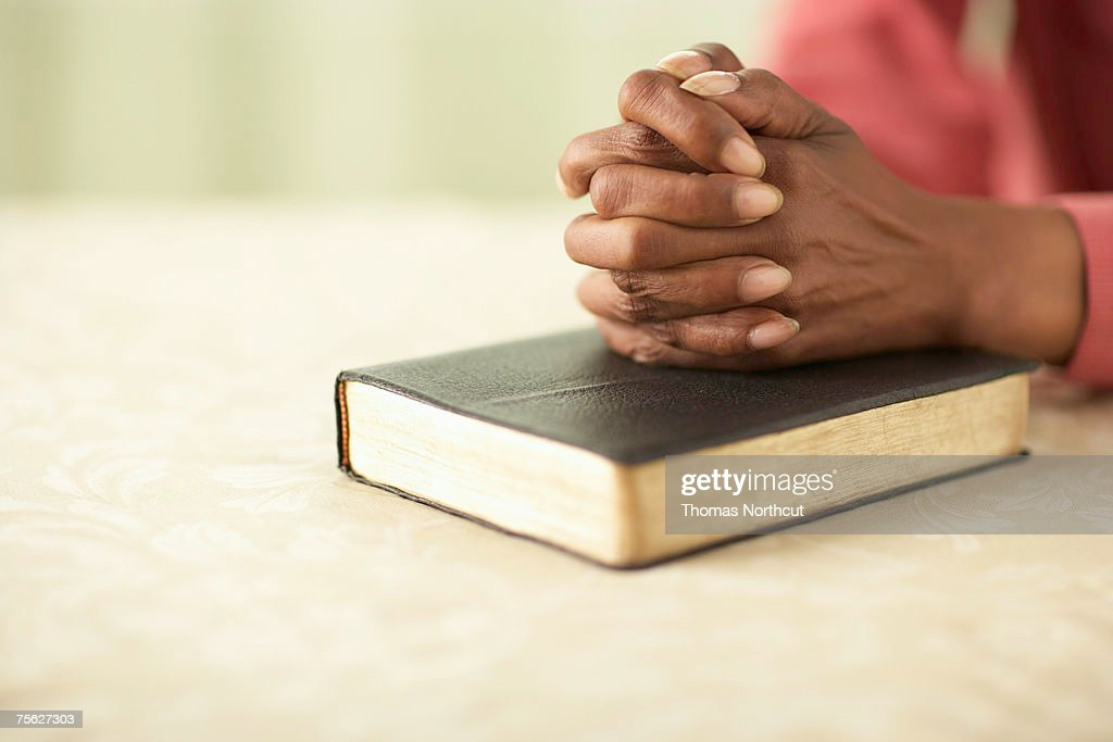 Senior woman sitting at table with hands clasped on Bible, close-up of hands : Stock Photo