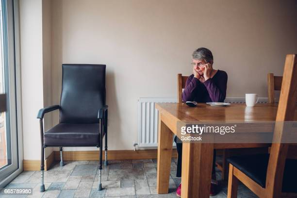 Senior Woman Sitting Beside an Empty Chair