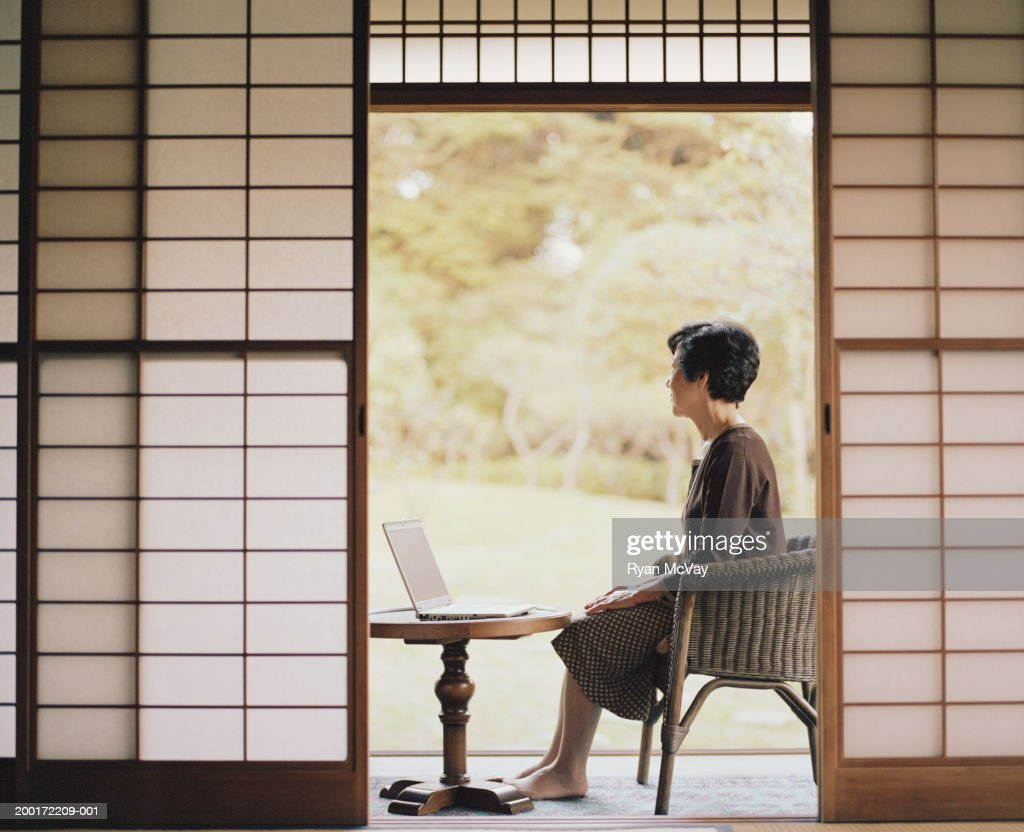Senior woman sitting beside open doorway, using laptop, side view : Stock Photo