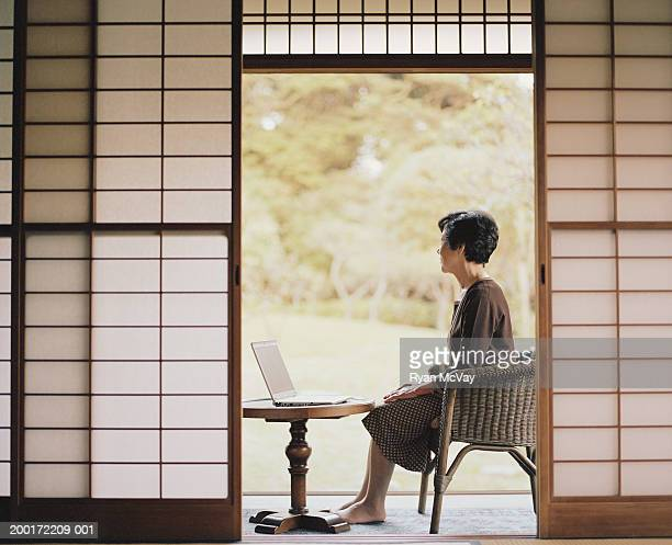 Senior woman sitting beside open doorway, using laptop, side view