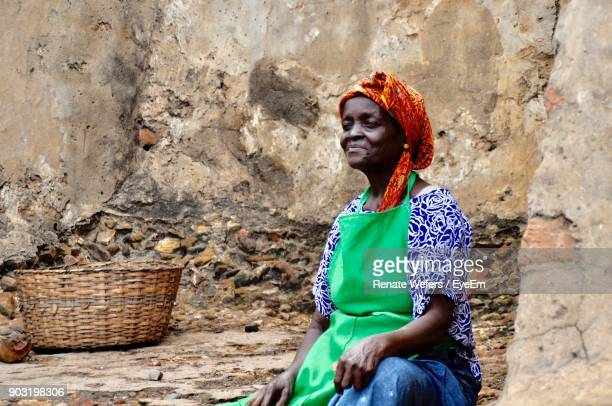 Senior Woman Sitting By Old Wall