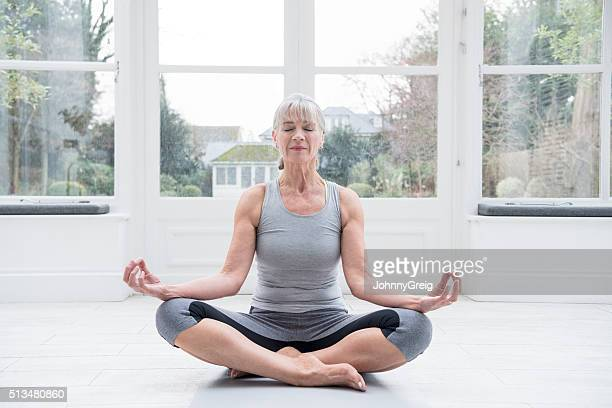senior woman sitting cross legged doing yoga at home - alleen één seniore vrouw stockfoto's en -beelden