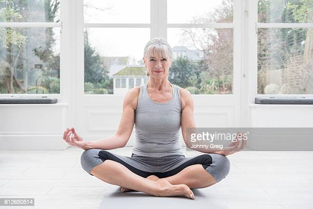 Senior woman sitting cross legged, meditating