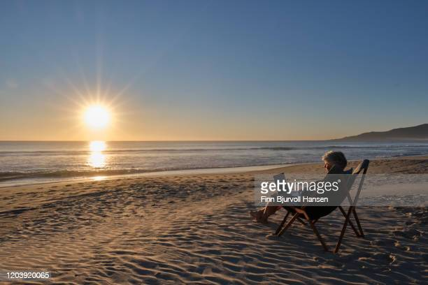 senior woman sitting in a chair at the beach at sunset working on her computer - finn bjurvoll stock pictures, royalty-free photos & images