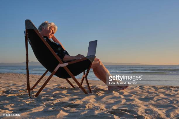 senior woman sitting in a chair at the beach at sunset working on her computer - finn bjurvoll - fotografias e filmes do acervo