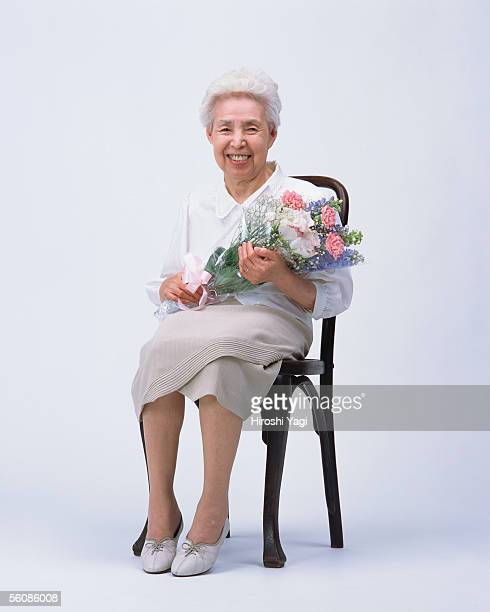 A senior woman sitting in a chair with flower bouquet
