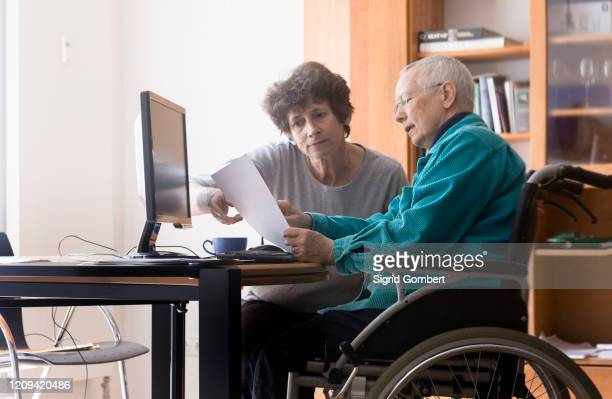 senior woman sitting in a wheelchair at a computer, helper assisting with paperwork. - sigrid gombert stock pictures, royalty-free photos & images