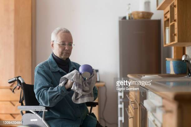 senior woman sitting in a wheelchair in her kitchen, drying up dishes. - sigrid gombert stock pictures, royalty-free photos & images
