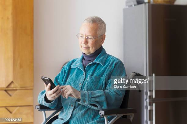 senior woman sitting in a wheelchair, using mobile phone. - sigrid gombert stock pictures, royalty-free photos & images