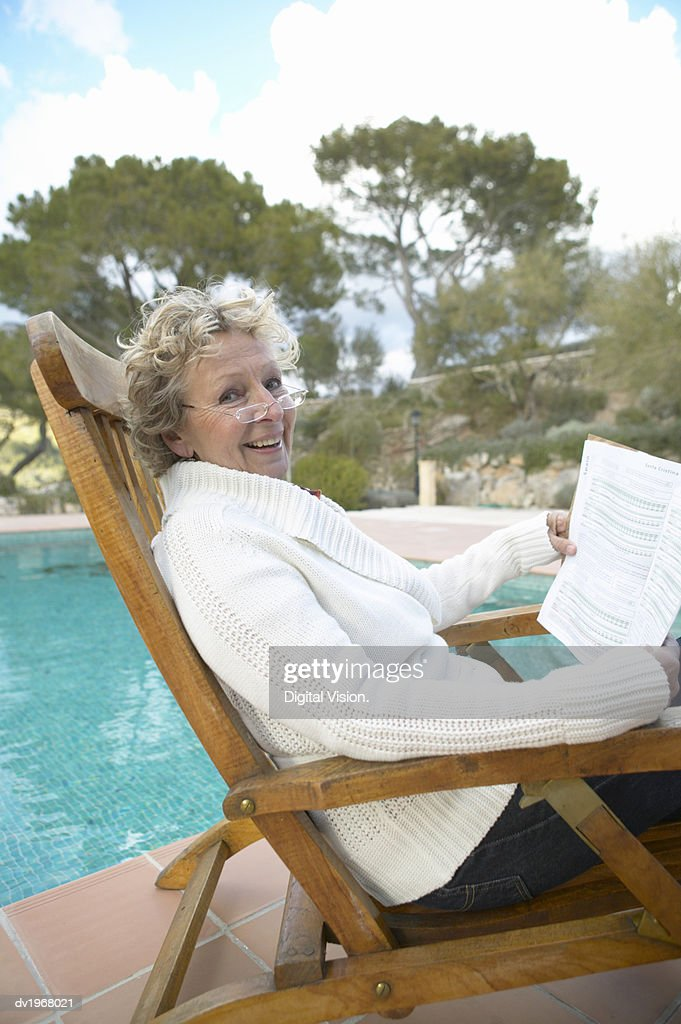 Senior Woman Sitting in a Wooden Chair by a Swimming Pool : Stock Photo