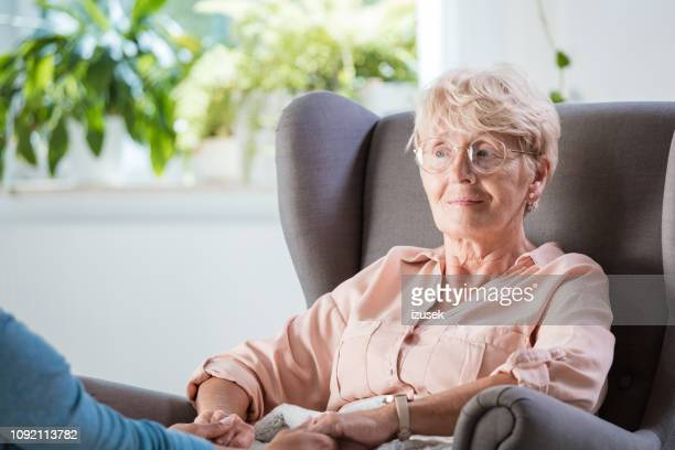 senior woman sitting in armchair at home - medical condition stock pictures, royalty-free photos & images
