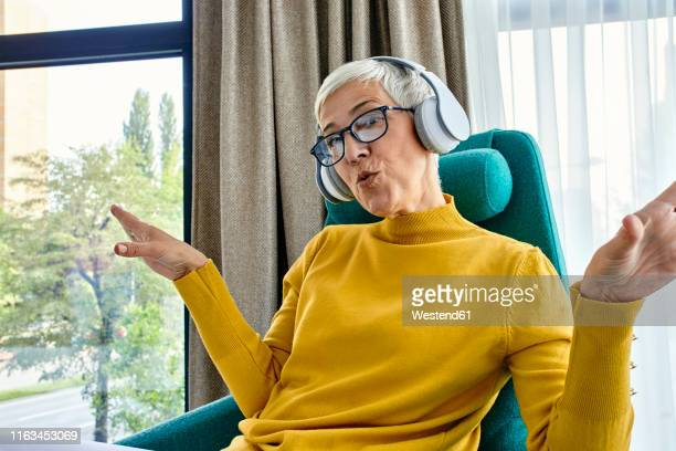 senior woman sitting in armchair, listening music with headphones - whistle stock pictures, royalty-free photos & images