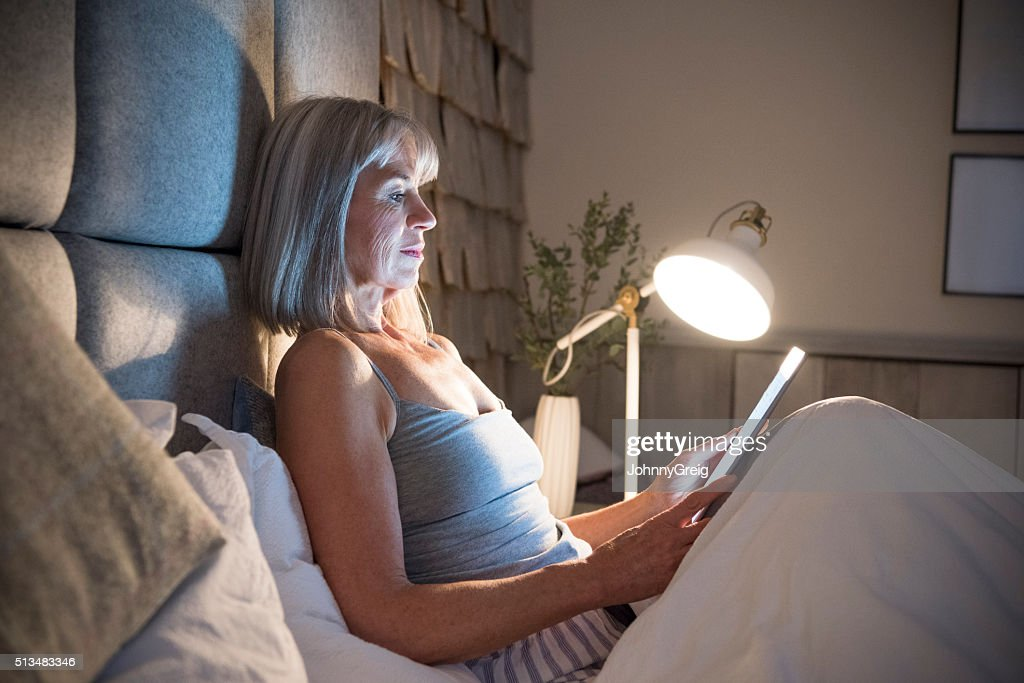 Senior mujer sentada en la cama por la noche con comprimido : Foto de stock