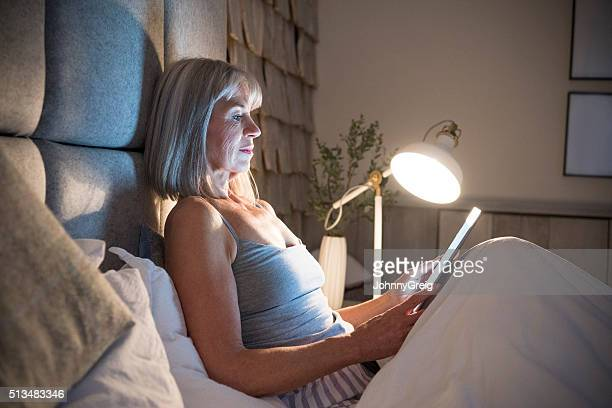 senior woman sitting in bed at night with tablet - electric lamp stock photos and pictures