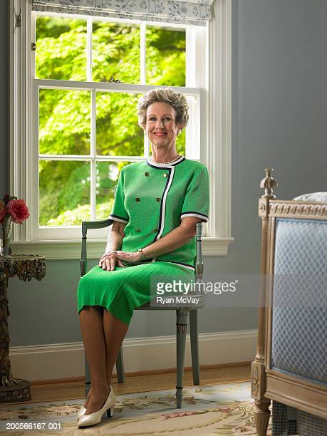 Senior woman sitting in bedroom, smiling, portrait