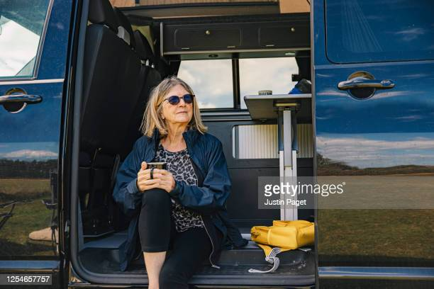 senior woman sitting in camper with a cuppa - camper van stock pictures, royalty-free photos & images