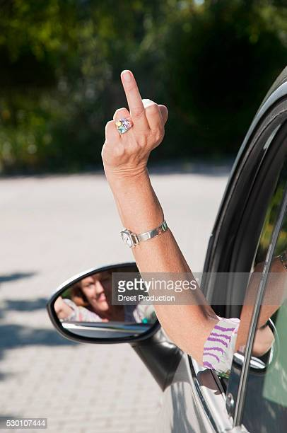 senior woman sitting in car and making rude sign - old lady middle finger stock pictures, royalty-free photos & images