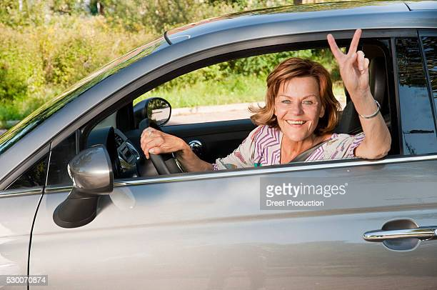 Senior woman sitting in car and showing victory sign