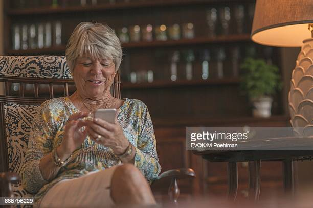 Senior woman sitting in chair and using smartphone