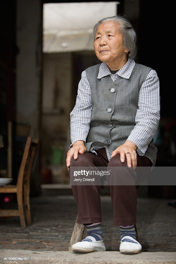 Senior woman sitting in doorway : Stockfoto
