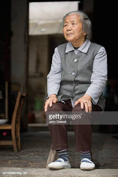 Senior woman sitting in doorway