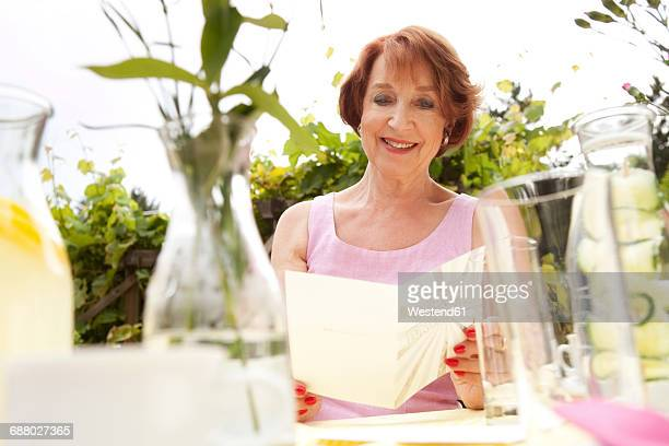 Senior woman sitting in garden, holding birthday card