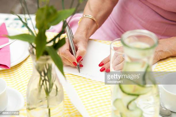Senior woman sitting in garden, writing birthday card