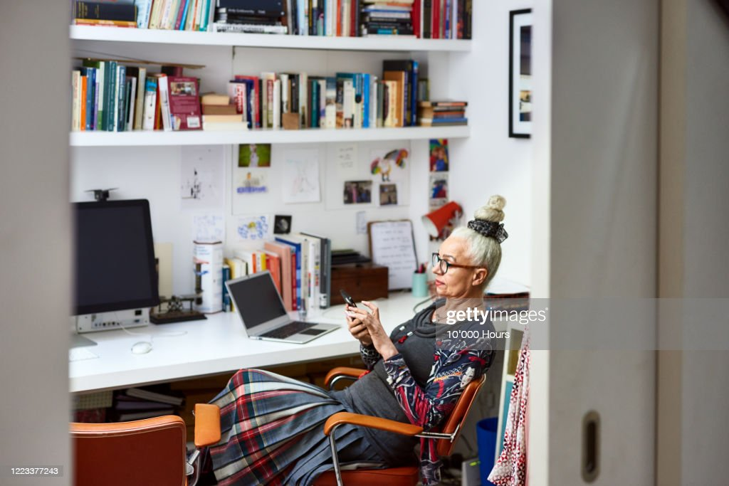 Senior woman sitting in home office using phone : Stock Photo