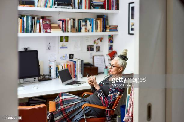 senior woman sitting in home office using phone - man made object stock pictures, royalty-free photos & images