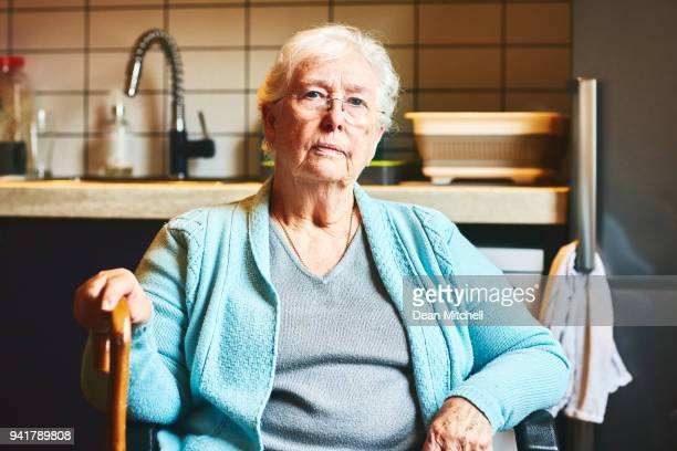 senior woman sitting in kitchen - old woman stock photos and pictures