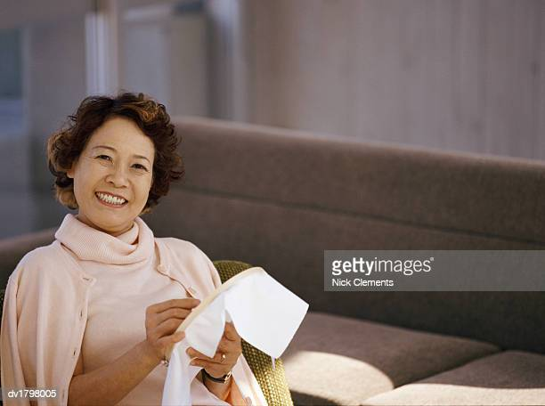 Senior Woman Sitting in Living Room Embroidering