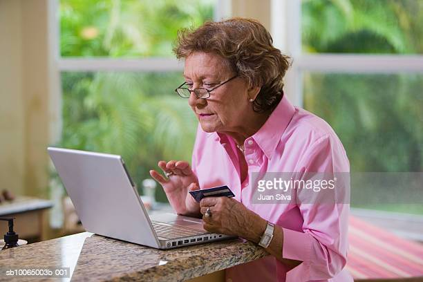 Senior woman sitting in room with laptop and credit card in hand